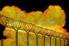 Explosion orange réaliste du feu derrière la barrière de barbelé de secteur restreint Image libre de droits