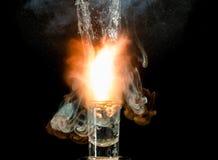 Explosionen av vatten i ett exponeringsglas på en svart bakgrund Hög bristning royaltyfri fotografi