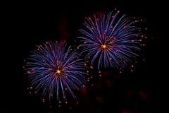 Explosionen von blauen und orange Feuerwerken Stockfotos