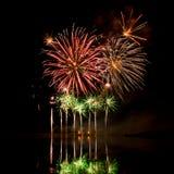 Explosionen von roten, orange und grünen Feuerwerken Stockfotos