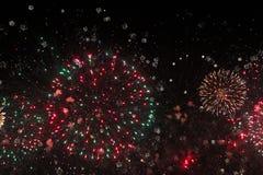 Explosiones rojas y verdes de los fuegos artificiales de la Navidad foto de archivo libre de regalías