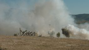 Explosions and clouds of smoke on the battlefield stock video footage