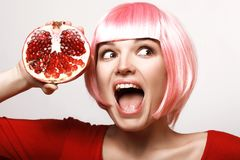 Explosive discounts, grenades. Girl with pomegranate. Pink hair. Beautiful girl with pomegranate, discounts. Makeup. Ripe and juicy. Pink hair Stock Images