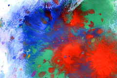 Explosive emotional drops of red, green, blue on white paper Royalty Free Stock Photo