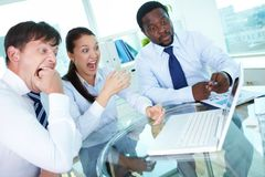 Explosive idea. Three astonished colleagues looking at laptop monitor at meeting Royalty Free Stock Photography