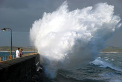 Explosive wave. Large wave colliding with a breakwater pier wall Stock Image