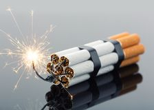 Explosives from cigarettes. With sparks on gray Royalty Free Stock Image
