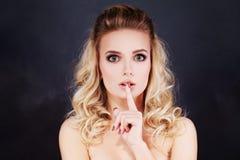 Explotación agrícola atractiva de la mujer su dedo a sus labios gesto para el silencio fotos de archivo