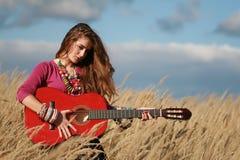 Explotación agrícola de la muchacha que toca la guitarra en campo Fotografía de archivo libre de regalías