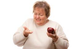Explotación agrícola mayor confusa Apple de la mujer y vitaminas Fotografía de archivo