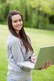 Explotación agrícola sonriente joven de la mujer su computadora portátil Imagen de archivo libre de regalías