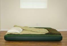 Explote la cama del colchón de aire con el saco de dormir y la almohada Fotos de archivo