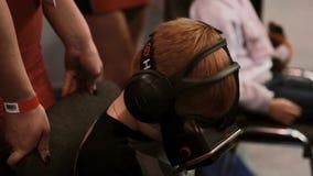 Expo da robótica 5 de novembro de 2016 de RÚSSIA, MOSCOU O rapaz pequeno do close-up usa vidros da realidade virtual vídeos de arquivo