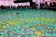 Expo 2015 Milano, beautiful Thailand pavilion. Beautiful Thailand pavilion with visitors standing around presentation pool and watching food pictures reflected Stock Image