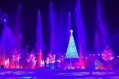 Exponerad julgran, strålar av vatten och färgrika ferieträd på natten i internationellt drevområde royaltyfri fotografi