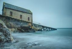 exponering long Avlagd livräddningsbåtstation på den Polpeor lilla viken, ödlapunkt, Cornwall royaltyfri bild