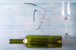 Exponeringsglas anmärker på en trätabell: en flaska och exponeringsglas Fotografering för Bildbyråer