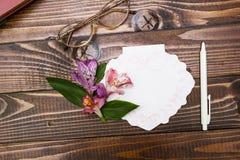 Exponeringsglas, anteckningsbok och blommor på träbakgrund arkivfoto