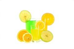 Exponeringsglas av äpple, apelsin och citronjuice med skivor bär frukt Royaltyfri Foto