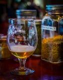 Exponeringsglas av öl bredvid dess ingredienser royaltyfri foto