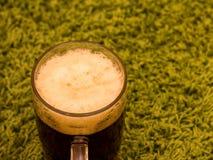 Exponeringsglas av öl för mörk brunt på grön bakgrund Royaltyfri Fotografi