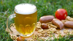 Exponeringsglas av öl, kringla och korvar arkivfoto