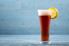Exponeringsglas av öl med citronen royaltyfria foton