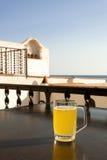 Exponeringsglas av öl med citronen nära havet Arkivfoto