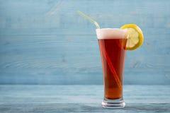 Exponeringsglas av öl med citronen och sipperen royaltyfri fotografi