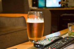 Exponeringsglas av öl med fjärrkontrollen i vardagsrummet Royaltyfria Bilder
