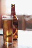 Exponeringsglas av öl med flaskan på tabellen arkivbild
