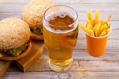 Exponeringsglas av öl med hamburgaren och småfiskar på träbakgrund Öl- och matbegrepp Öl och mat arkivbild