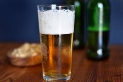 Exponeringsglas av öl med pistaschen och gröna flaskor i bakgrunden royaltyfria foton