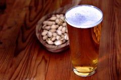 Exponeringsglas av öl med pistaschen arkivfoton