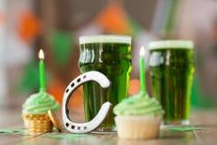 Exponeringsglas av öl, muffin, hästsko och guld- mynt Royaltyfri Fotografi