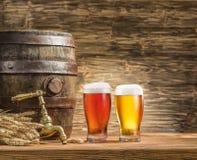 Exponeringsglas av öl och öl barrel på trätabellen royaltyfria bilder