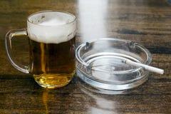 Exponeringsglas av öl och ett askfat Arkivbild