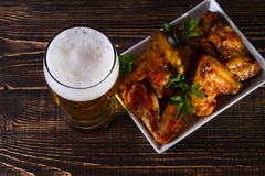 Exponeringsglas av öl och fega vingar på mörk träbakgrund Royaltyfri Foto