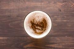 Exponeringsglas av öl på en träbakgrund Top beskådar royaltyfri bild
