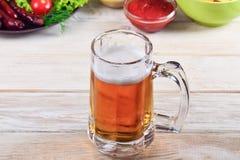 Exponeringsglas av öl på en trätabell Fotografering för Bildbyråer