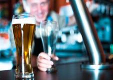 Exponeringsglas av öl på stångräknare mot bakgrund av den vänliga barten arkivbilder