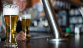 Exponeringsglas av öl på stångräknare mot bakgrund av den vänliga barten arkivfoton