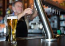 Exponeringsglas av öl på stångräknare mot bakgrund av den vänliga barten royaltyfria foton