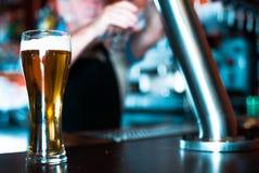 Exponeringsglas av öl på stångräknare mot bakgrund av den vänliga barten arkivfoto
