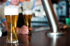 Exponeringsglas av öl på stångräknare mot bakgrund av den vänliga barten fotografering för bildbyråer