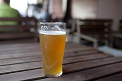 Exponeringsglas av öl på tabellen Royaltyfri Fotografi