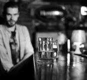 Exponeringsglas av öl Exponeringsglas av utkastöl på suddig stångbakgrund Royaltyfri Fotografi