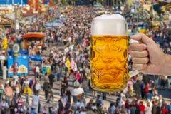 Exponeringsglas av ölinnehavet i hand på Oktoberfest i Munich arkivfoto