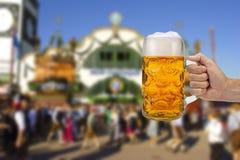 Exponeringsglas av ölinnehavet i hand på Oktoberfest i Munich royaltyfri foto