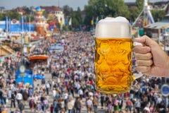 Exponeringsglas av ölinnehavet i hand på Oktoberfest i Munich arkivbild
